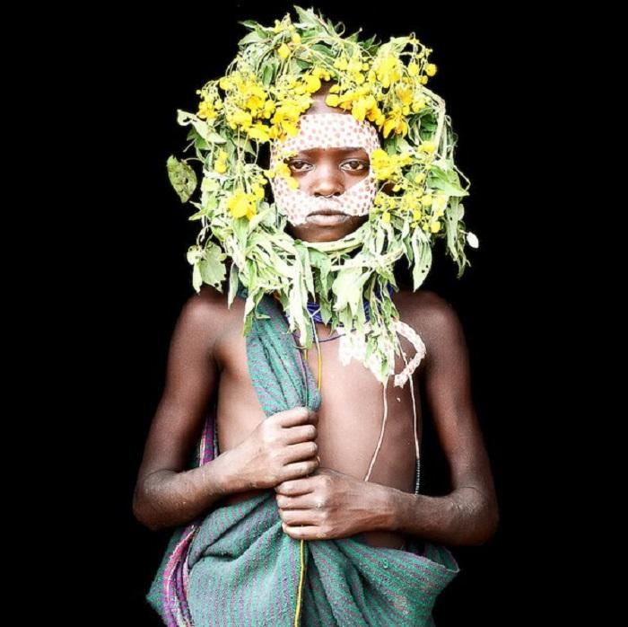 Молодой мальчик из племени Сури показывает свои традиционные краски.