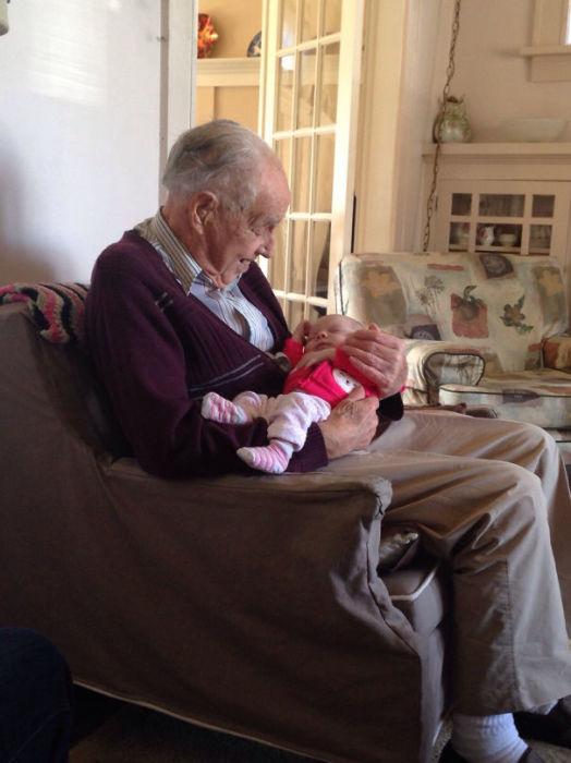 98-летний дедушка впервые держит на руках свою внучку, которой исполнилась 1 неделя.