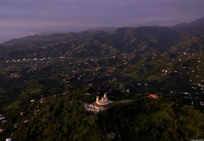 Среди тихих лесистых холмов недавно отреставрированный храм блестит и сверкает в лучах восходящего солнца.