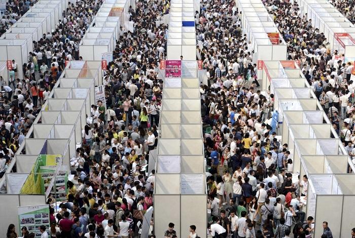 Тысячи лиц, ищущих работу, рассматривают стенды на ярмарке вакансий в городе Чунцин.