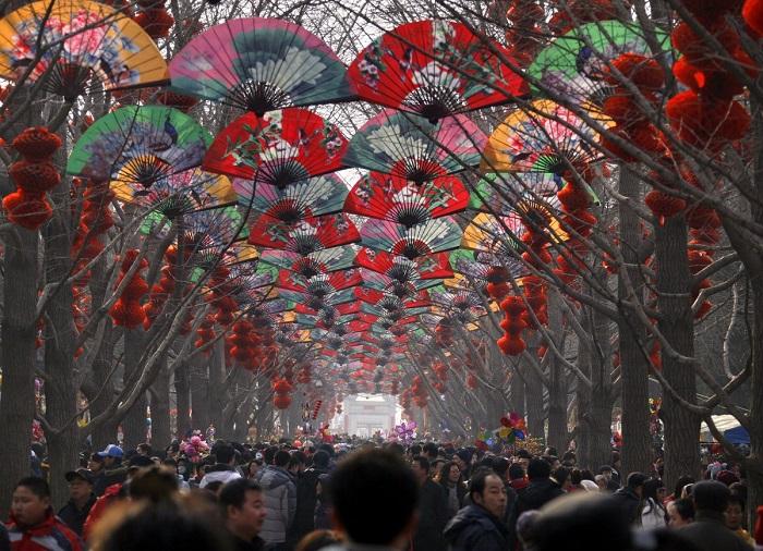 Толпы людей ходят среди деревьев, украшенных красными фонарями на храмовой ярмарке в честь празднования китайского Нового года в Пекине.