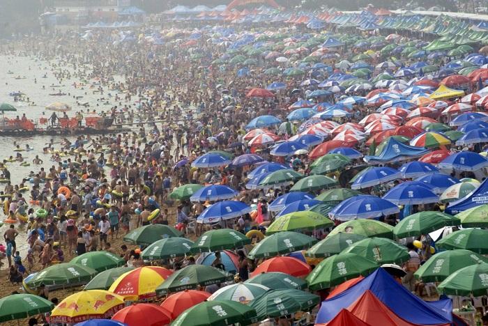 Люди толпятся на пляже в городе Далянь, провинция Ляонин, спасаясь от летней жары.