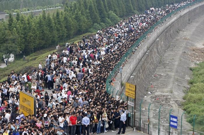 Очередь из желающих посмотреть на высокий поток около берега реки Цяньтан в городе Ханчжоу, провинция Чжэцзян.