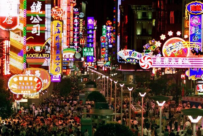 Покупатели толпятся под красочными неоновыми огнями вдоль оживленной Нанкинской улицы Шанхая.