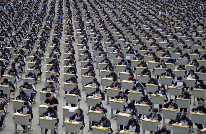 Студенты сдают экзамен на детской площадке средней школы под открытым небом в Yichuan, провинция Шэньси. Более 1700 первокурсников приняли участие в экзамене в 2015 году.