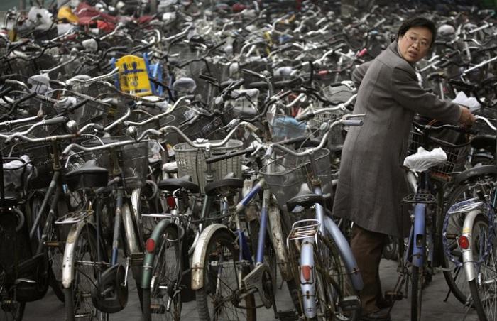 Женщина забирает свой велосипед на стоянке за станцией метро в Пекине.