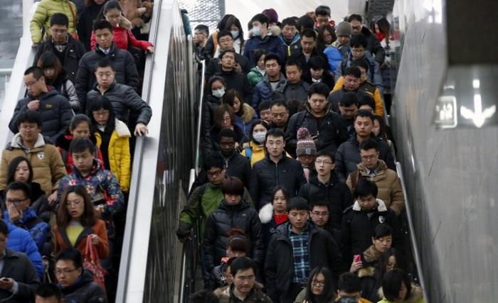 Люди спускаются на эскалаторе и сходят по лестнице, направляясь к платформе метро в час пик в Пекине.