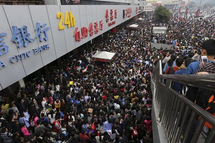 Пассажиры на переполненном железнодорожном вокзале Чжэнчжоу в первый день праздника по случаю годовщины Дня образования КНР.
