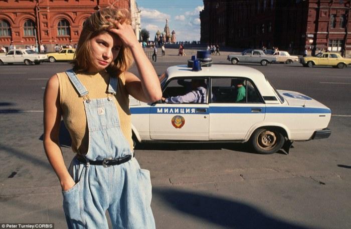 Катя курсирует по улицам Москвы в поисках клиентов, а мимо нее проезжает милицейская машина в 1991 году.