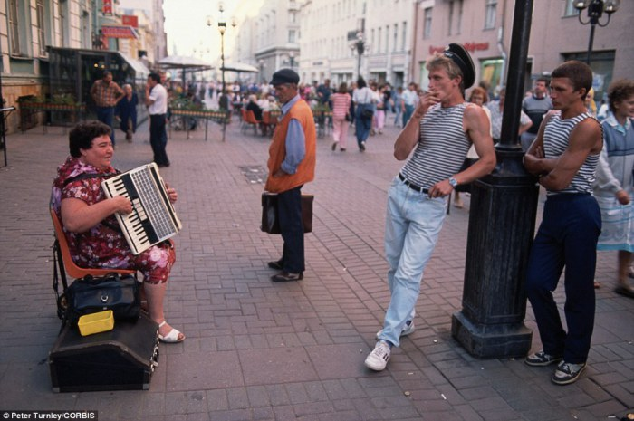 Женщина играет на популярной пешеходной улице Арбат в Москве, а несколько стоящих мужчин ее слушают.