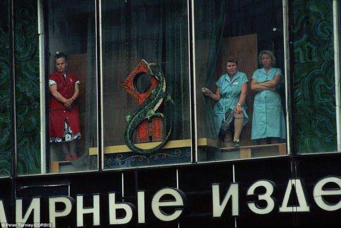 Женщины наблюдают за похоронами из окна ювелирного магазина после неудачной попытки государственного переворота в Москве.