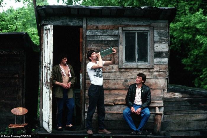Мужчины выпивают у сарая в городе Новокузнецк, который в начале 90-х одолевали серьезные экономические проблемы.