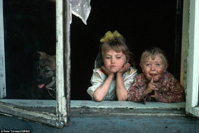 Двое детишек выглядывают из окна в горно-металлургическом городке в Сибири.