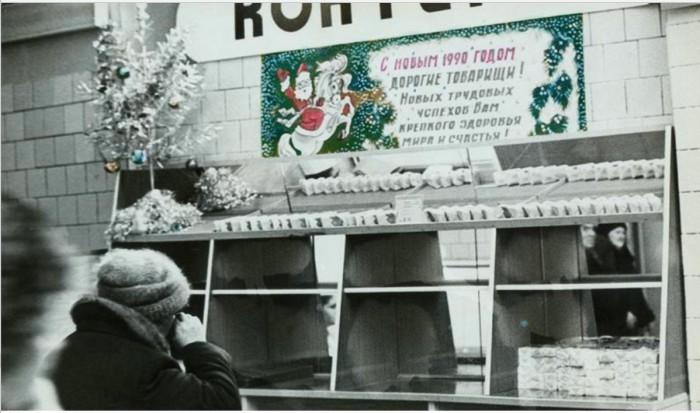 В магазине развешаны новогодние гирлянды и поздравительные плакаты.  1989 год.