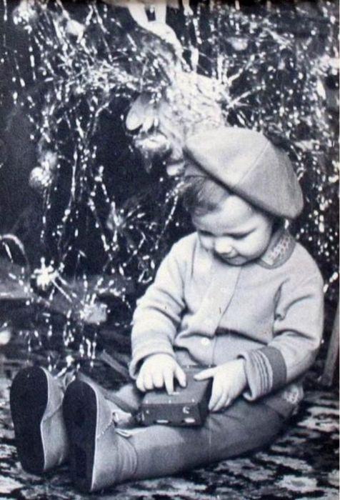Ребенок рассматривает новогодний подарок прямо под елкой. 1960 год.