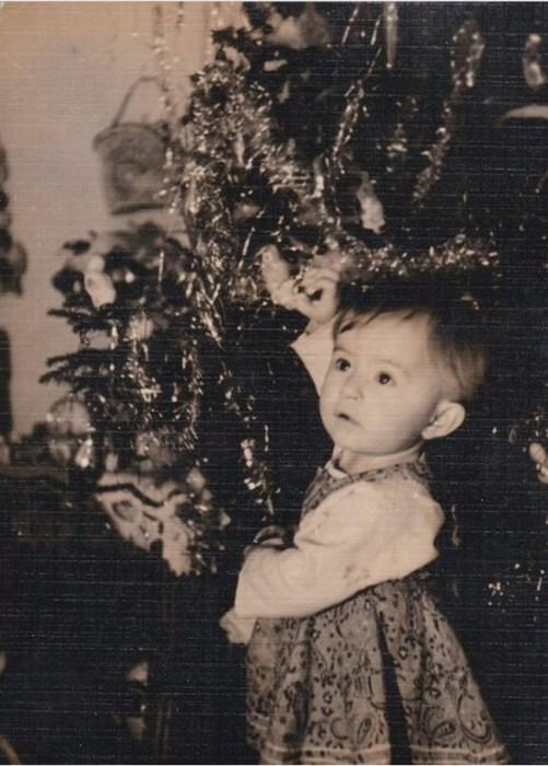 Все надо попробовать - и игрушки, и гирлянды, и колючую елочку.  1962 год.