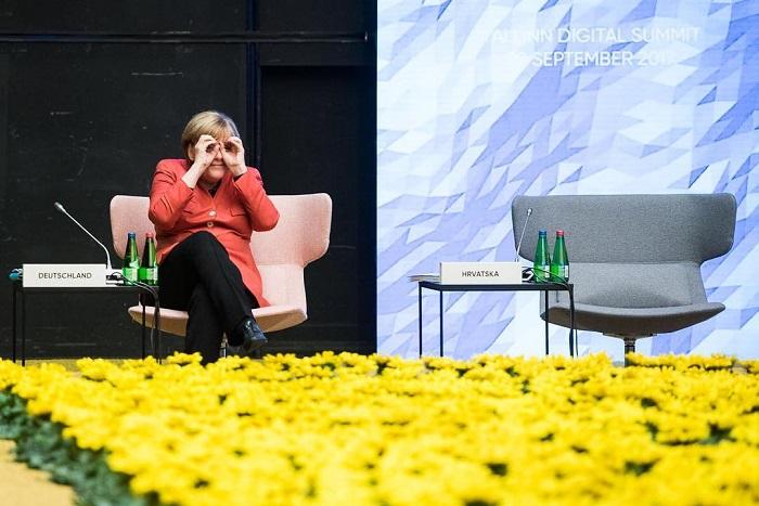 На Европейском саммите в Таллине Меркель шутливо отреагировала на собеседника, который находился в другом конце зала, и изобразила руками бинокль.