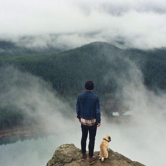Хозяин и пес смотрят вдаль с большого утеса.