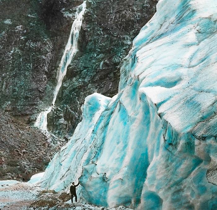Турист стоит рядом с ледником и водопадом.