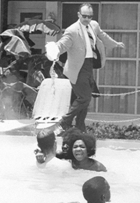 Владелец отеля выливает кислоту в бассейн, в то время как афроамериканцы плавают в нём, 1964 год.