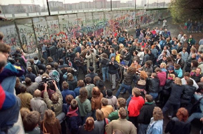 11 ноября, 1989 года, жители западного Берлина смотрят как люди стараются разрушить секцию стены, что открыть новый проход для пересечения границы.