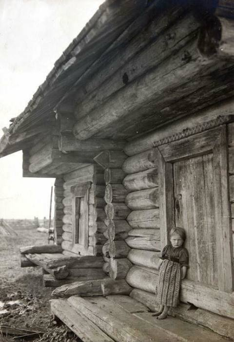 Маленькая девочка подпирает избу. Автор фотографии: неизвестен.