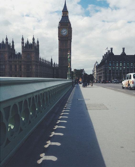 Часовая башня Вестминстерского дворца в Лондоне бросает тень на мостовую.