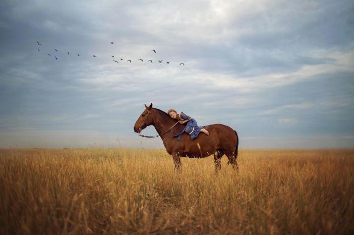 Взаимное доверие лошади и рыжеволосой девочки.