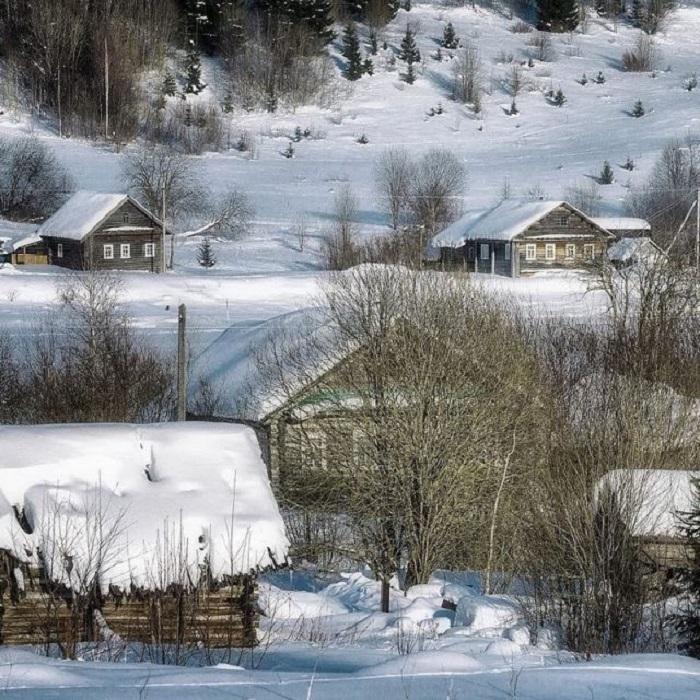 Сонные деревянные домики русской деревни, заметенные снегом.