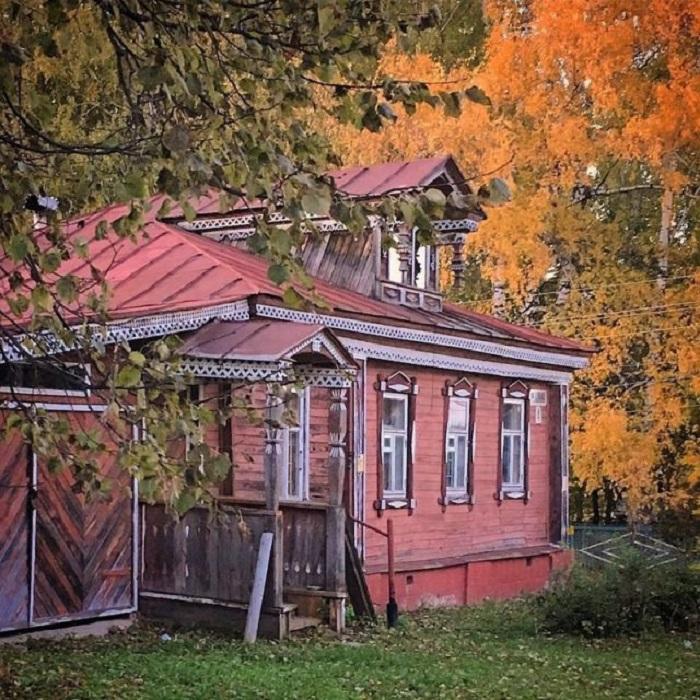 Деревенский домик с резным крыльцом не уступает яркостью красок осенним деревьям.