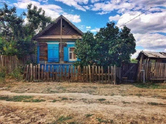 Маленький деревянный домик с окрашенными синими ставнями притаился за самодельным редким заборчиком.