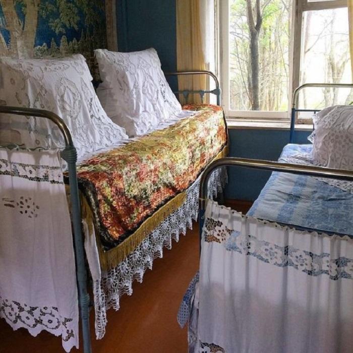 Простыни с кружевами и ажурные «шторки» на железных кроватях.