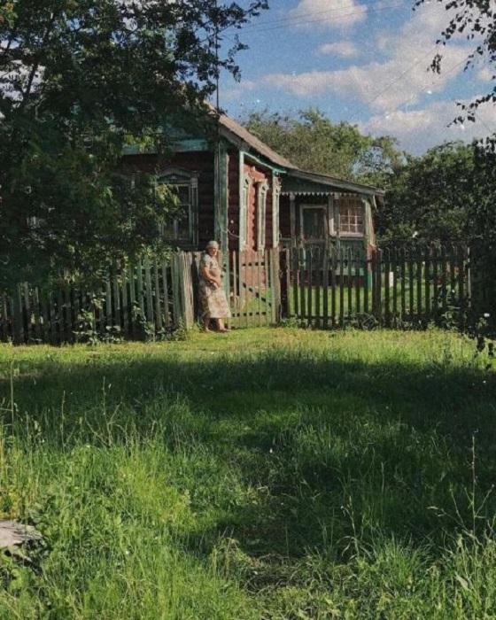 Пожилая жительница русской деревушки греется на солнышке возле своего двора.
