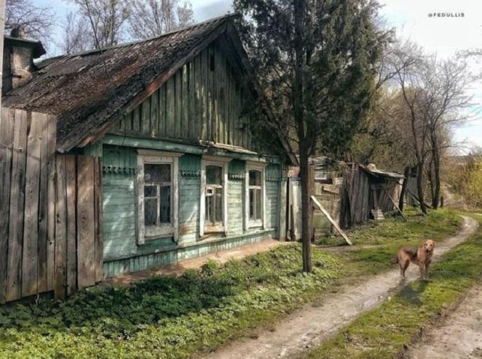 Деревенская дорога, проходящая практически под окнами деревянного дома.
