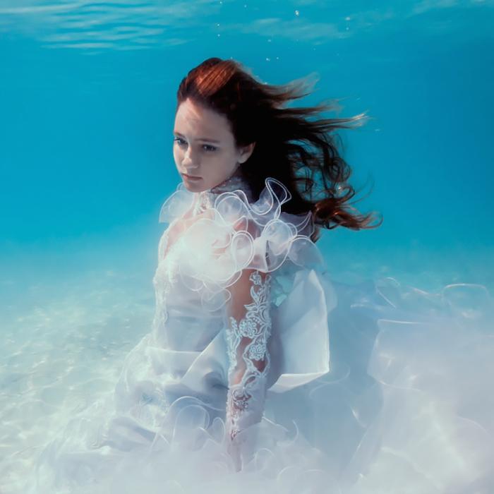Белое свадебное платье сливается с океанским дном и создается впечатление единого целого.