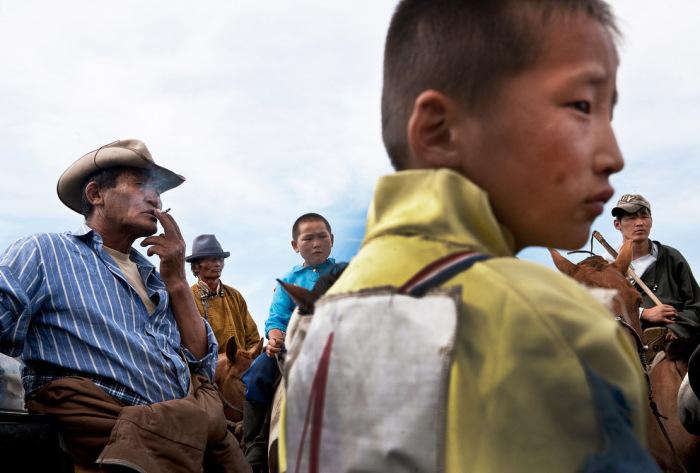 Участники соревнований, зрители и владельцы лошадей на традиционном монгольском празднике Надом.