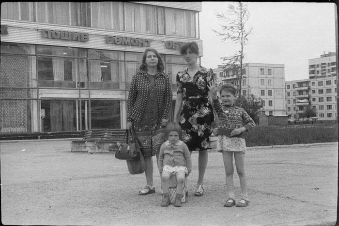 Молодые женщины с детьми на фоне Дома быта – обязательного элемента каждого города.