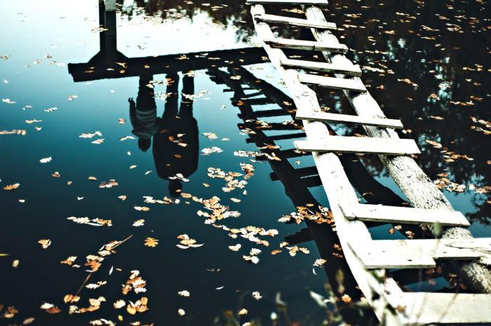 Зеркальная поверхность осеннего озера отображает силуэты людей. Автор фотографии: Екатерина Шуляк.