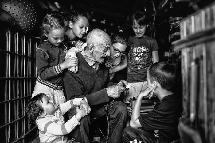 Дедушка в окружении своих внуков что-то активно объясняет и показывает. Автор фотографии:Анна Волкович.