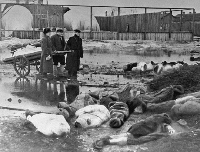 Трое мужчин хоронят жертв блокады Ленинграда.