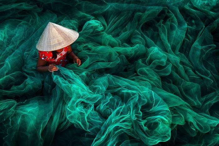 Женщина в небольшой рыбацкой деревушке Фанранг на юге Вьетнама делает традиционную рыболовную сеть. Автор фотографии: Дэнни Йен Вонг Син (Danny Yen Sin Wong).