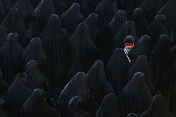Мусульманская женщина с сыном принимают участие в похоронах Иса Радхи. Автор фотографии: Иса Эбраим (Isa Ebrahim).