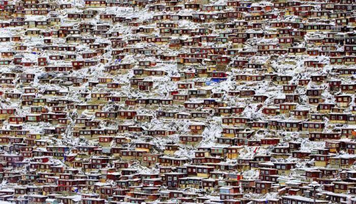 Красные дома лам и монахинь покрыты обильным снежным покровом. Автор фотографии: Кингджин Рон (Qingjun Rong).