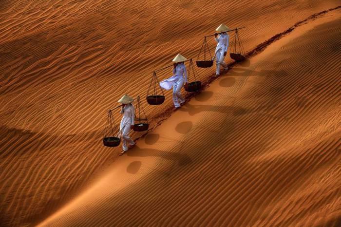 Три девушки в традиционной одежде, спускаются по склону дюны, неся на себе коромысла с корзинами. Автор фотографии: Дэнни Ен Грех Вонг (Danny Yen Sin Wong).