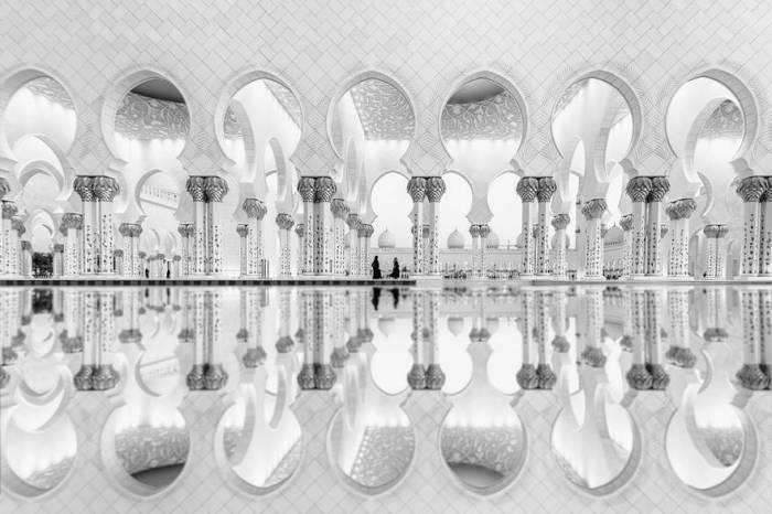 Образы двух женщин отражаются на воде и придают возвышенности геометрии и архитектуре Большой Мечети Шейха Зайеда. Автор фотографии: Али Аль Джайри (Ali Al Jajri).