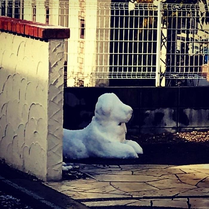 Скульптуру из снега специально создали возле стены, чтобы защитить от солнечных лучей.