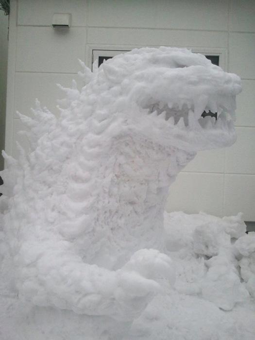 Небольшой, но довольно детализированный доисторический ящер-монстр Годзилла из снега расположился в одном из дворов.