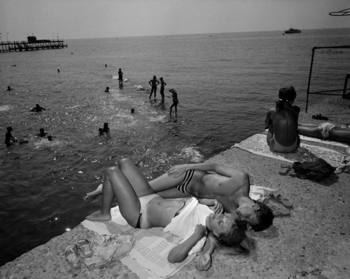 Люди купаются и загорают возле берега.