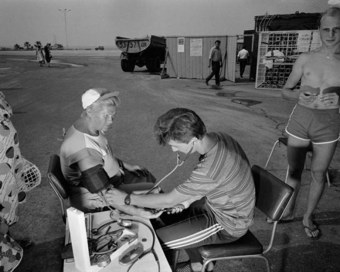 Работник медпункта измеряет давление пожилой женщине.