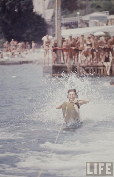Радостные отдыхающие наблюдают за девушкой на водных лыжах.